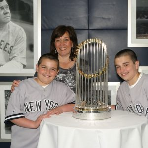 Family taking a picture next to the NY Yankees' 2010 Commissioner's Trophy in ny